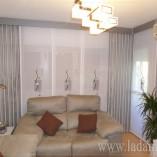 Paneles japoneses bordados y estor en salón moderno.
